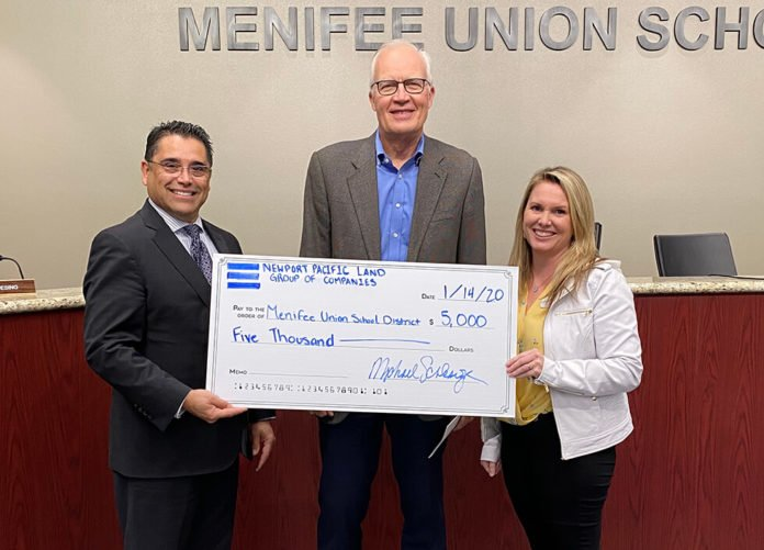 Steve Kennedy accepts a donation from Michael Schlesinger of Newport Pacific Land