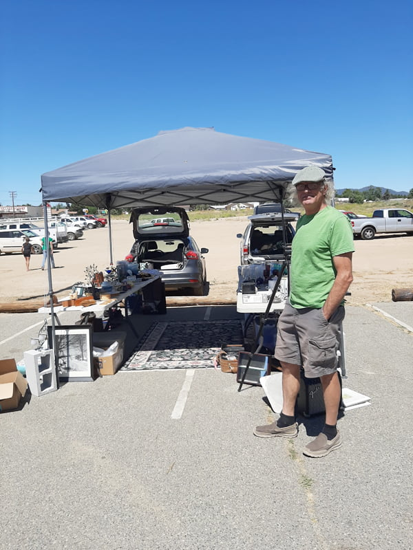 Man besides tent in parking lot with goods underneath