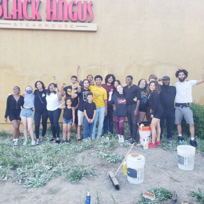 Group of members of Black Lives Matter posing in front of the wall they cleaned of graffiti